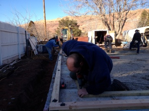 Our homeowner Lorenzo nailing down a bottom plate. The anchor bolts (with nuts and washers attached) are visible in the foreground at the corner.