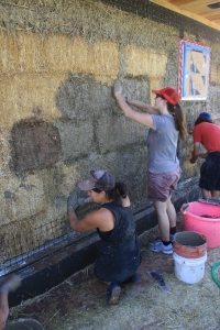 Josefina, Molly and Jeffrey apply a clay slip to the bales as a binding agent between plaster and the straw.