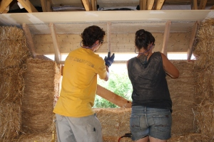 Here is a wonderfully overexposed shot of Chris and Josefina attaching the lath (aka- blood lath, so called for it's sharp edges) to the multi-cut block running at an angle between the window frame and the drywall. (Note that the drywall here is installed as a fire retardant barrier between the living space and the wall/attic area.