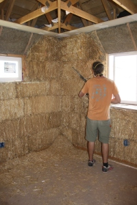 Dan and Chainsaw trim to plum the interior face of the bale wall, creating a surface ready for even-handed plastering.