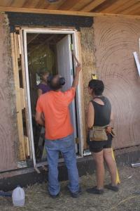 Doug assists Josefina and Brita installing a door.