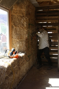 Anna angle grinds a notch into the bedroom wall for future built-in shelving. We have found the angle-grinder to be an effective though problematic means of trimming and shaping set bales. A better tool may be at hand: an electric sheep shearer. With the look of an oversized beard trimmer, the shearer is used by local electricians to cut notches into bales to set panel and switch boxes. It is just as, if not more, effective as the angle grinder, gripping the cutting the straw with a forward face that bears nothing of the sense of danger and volatility of a wildly spinning grinder blade. Plus, it makes less of a mess of straw that the grinder usually sends crach course into clothing and lungs. In all ways it seems the direction to go for interior bale trimming, notch-cutting and other shaping tasks. CR could stand a few in the arsenal.