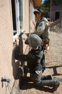 Grace and Josefina install exterior sills beneath all windows. A few inches of plastic surface tied directly to the window frame.
