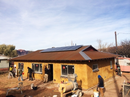A beautiful yellow color wash beneath a corrugated metal roof with - wait! Are those solar panels?! YES!